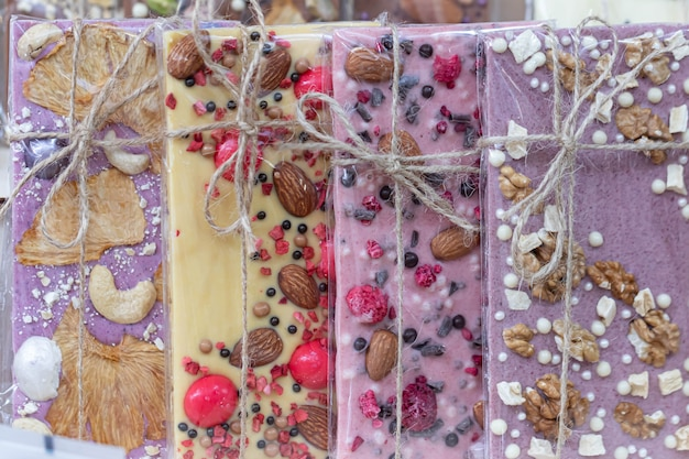 Un set di vari cioccolatini (bianco, rosa, marrone, amaro, latte) avvolto in una confezione trasparente con un fiocco in corda di iuta