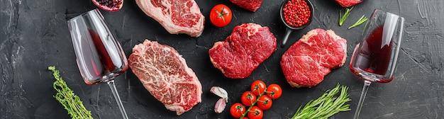Insieme di varie bistecche di carne crude classiche e alternative con bicchieri di vino rosso su sfondo nero vista dall'alto. banner di grandi dimensioni.