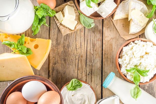 Set di vari prodotti lattiero-caseari freschi - latte, ricotta, formaggio, uova, yogurt, panna acida, burro su fondo di legno
