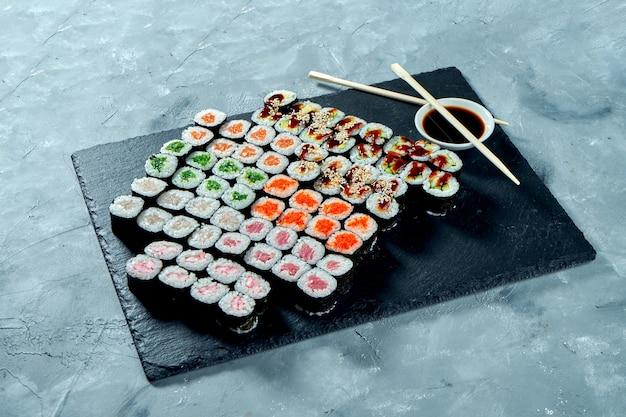 Set di vari maki sushi con salmone, anguilla, cetriolo, avocado, tonno, wakame, pesce persico su una tavola di ardesia nera. sfondo grigio