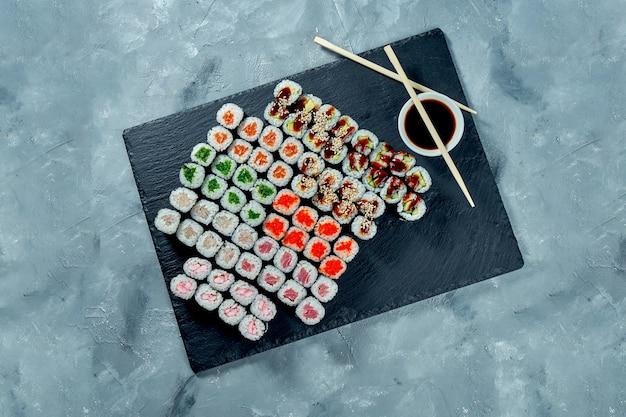 Set di vari sushi maki con salmone, anguilla, cetriolo, avocado, tonno, wakame, pesce persico su una tavola di ardesia nera. sfondo grigio