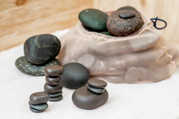 Insieme di varie pietre da massaggio sul tavolo nel salone della stazione termale