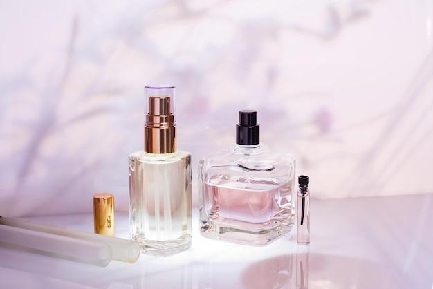 Insieme di varie bottiglie di profumo con spray sul rosa