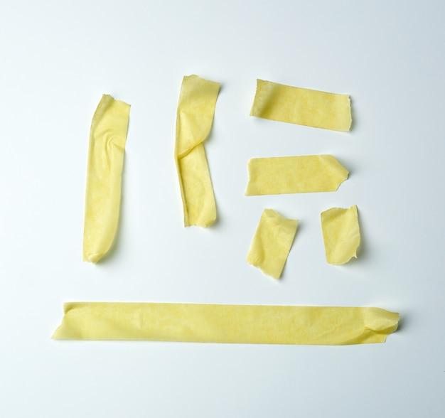 Insieme di vari pezzi di nastro di carta appiccicoso giallo su bianco