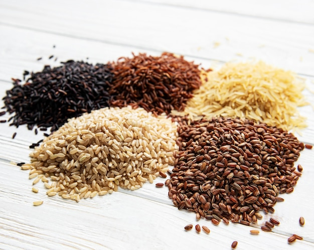 Set di vari tipi di riso su fondo di legno bianco nero basmati marrone e riso misto rosso