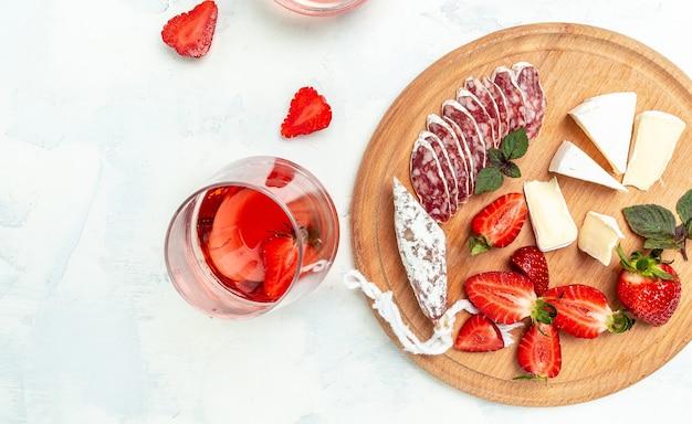 Set di varie fette di salsicce di salame fuet stagionato a secco spagnolo, formaggio camembert, fragole e bicchiere di vino rosato su sfondo bianco. banner, posto ricetta menu per testo, vista dall'alto.