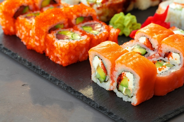 Insieme di vari rotoli di sushi serviti su sfondo grigio vicino