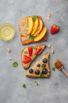 Set di vari toast con burro di arachidi; miele; menta; arachidi, nettarine, mirtilli e fragole