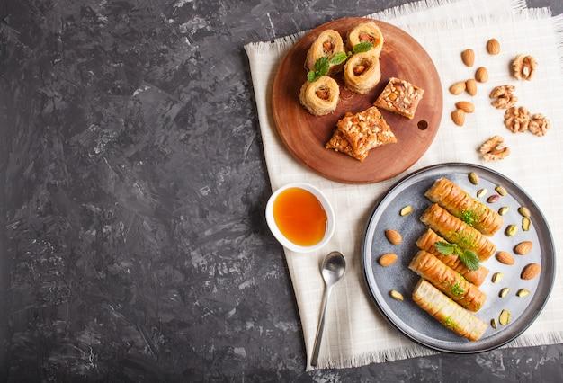Insieme di vari dolci tradizionali arabi: baklava, kunafa, basbus in piatti di ceramica su un cemento nero. vista dall'alto.