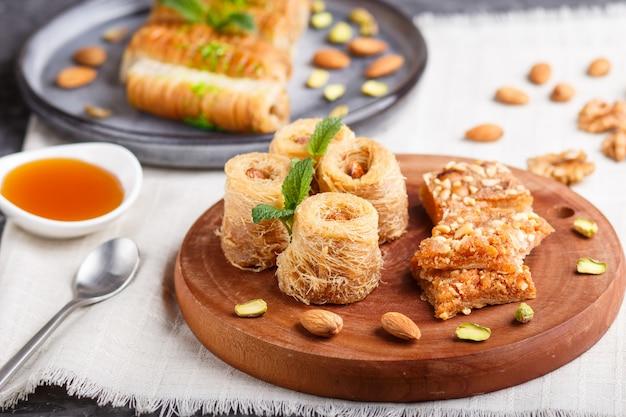 Insieme di vari dolci tradizionali arabi: baklava, kunafa, basbus in piatti di ceramica su un cemento grigio. vista laterale.