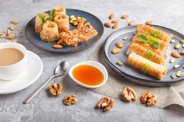 Set di vari dolci tradizionali arabi: baklava, kunafa, basbus in ceramica piatti vista dall'alto.