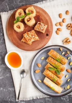 Insieme di vari dolci arabi tradizionali: baklava, kunafa, basbus in piatti di ceramica