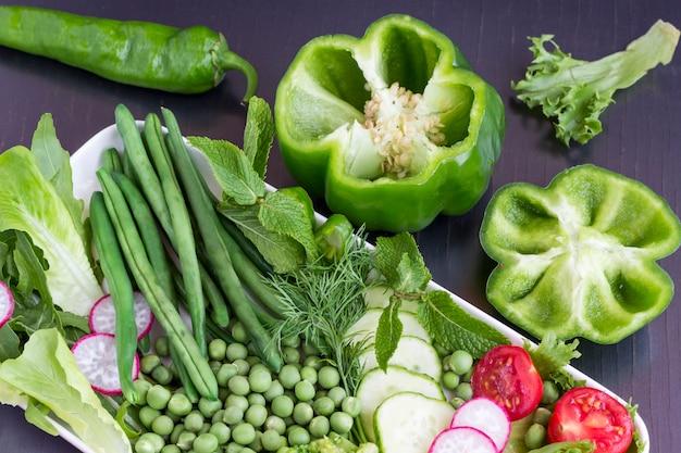 Un insieme di verdure: piselli, peperoni verdi, ravanelli, cetrioli.