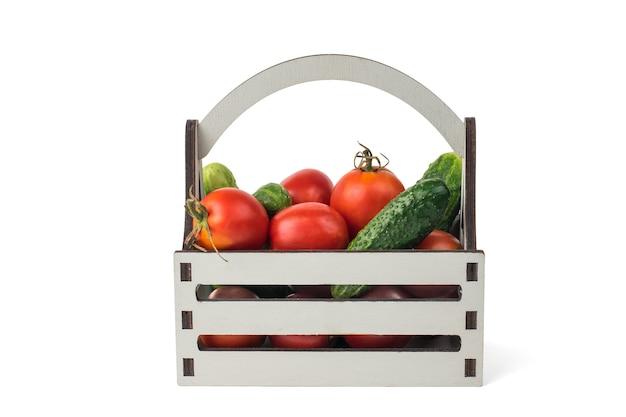 Un insieme di verdure in una scatola di legno isolata su uno sfondo bianco.