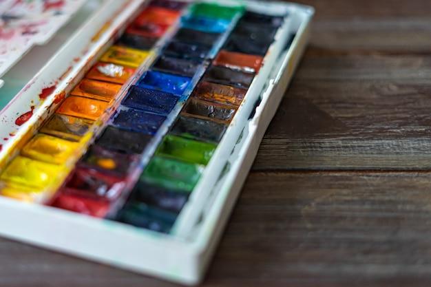 Insieme delle pitture e dei pennelli dell'acquerello per il primo piano di verniciatura.