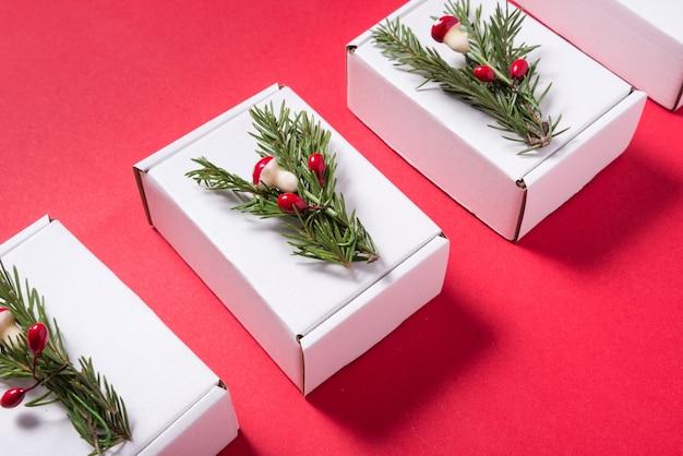 Set di scatole di cartone bianche decorate con ornamento albero di natale su sfondo rosso