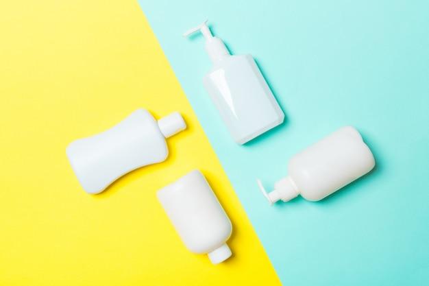 Insieme dei contenitori cosmetici bianchi isolati su fondo giallo e blu, vista superiore con lo spazio della copia. il gruppo di contenitori di plastica della bottiglia del bodycare con spazio vuoto per voi progetta