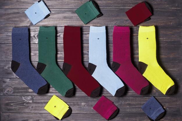 Set di calzini colorati casual invernali, flatlay su uno sfondo di legno