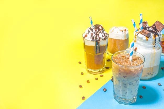 Set con diverse bevande al caffè estivo ghiacciato - espresso, frappe, latte, cappuccino, con panna montata, sciroppo e ghiaccio tritato, in vari bicchieri e tazze su sfondo blu giallo brillante alla moda