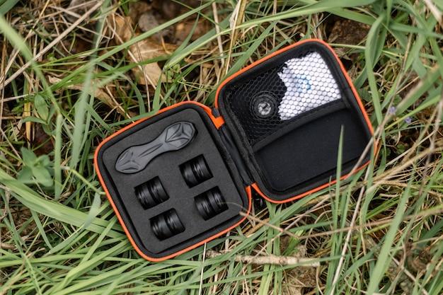 Un set con obiettivi per una fotocamera di un telefono cellulare si trova sull'erba verde.