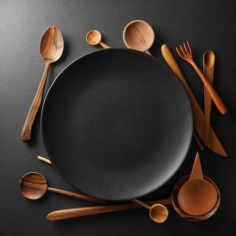 Impostazione piatto nero vuoto e cucchiaio di legno, forchetta, coltello su un tavolo nero.