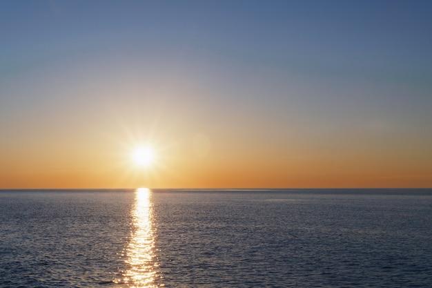 Il sole al tramonto va in mare all'orizzonte con una traccia di luce e riflessi sul mare.