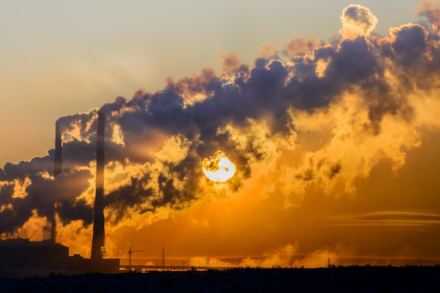 Il sole al tramonto si fa strada attraverso il fumo denso dei camini delle fabbriche. tundra polare, inverno.