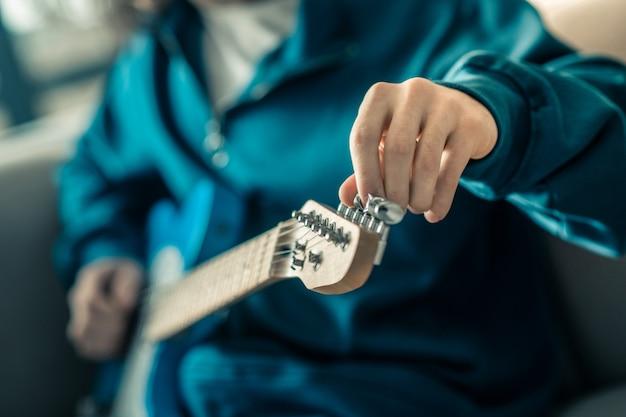 Strumento di installazione. ragazzo esperto in felpa blu che tira le corde della sua chitarra elettronica mentre la prepara per la ripetizione