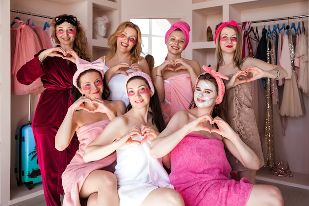 Sette belle giovani donne in asciugamani rosa, con bende cosmetiche in testa