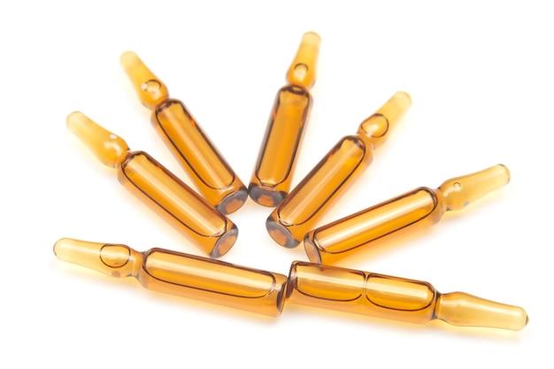 Sette fiale di vetro per uso medico per iniezione di droga su uno sfondo bianco