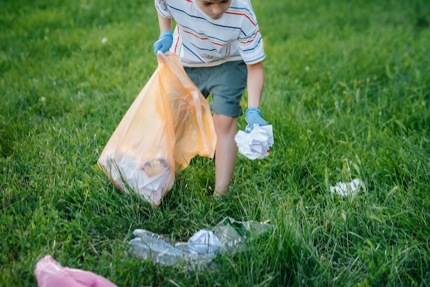 Un bambino di sette anni al tramonto è impegnato nella raccolta dei rifiuti nel parco. cura dell'ambiente, riciclaggio.