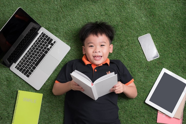 Bambino di sette anni che legge un libro sdraiato sull'erba