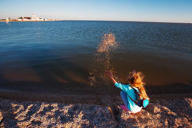 Ragazza di sette anni sulla spiaggia all'ora del tramonto.