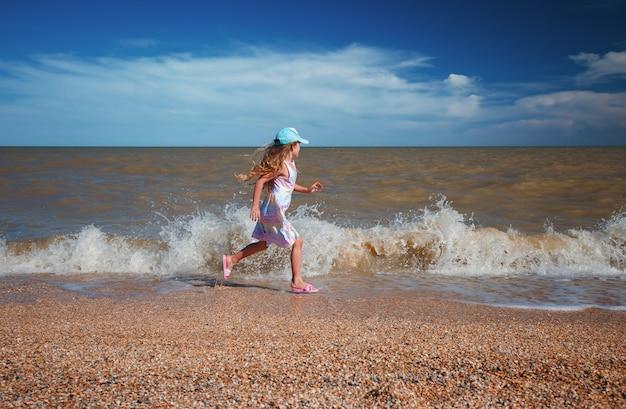 Ragazza di sette anni in abito estivo che corre lungo il mare al giorno pieno di sole.