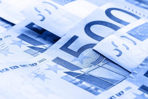 Diverse banconote e monete da 500 euro sono adiacenti. foto simbolica per wealt.euro moneta in equilibrio su pila con sfondo di banconote.