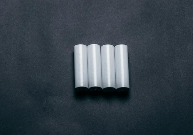 Diverse batterie aa bianche vuote su spazio carta nera