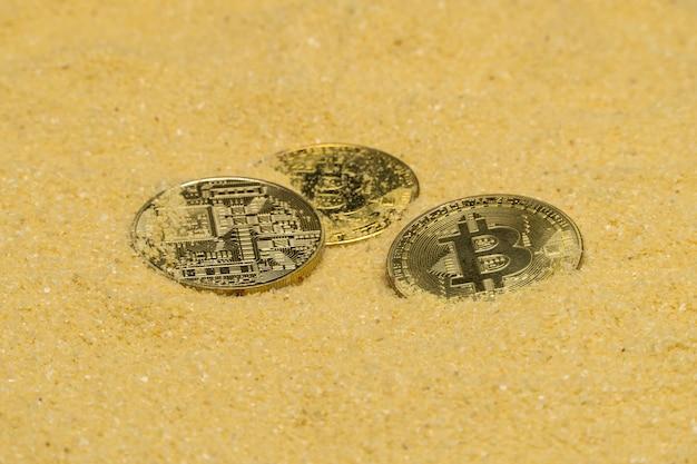 Diverse monete cripto bitcoin su sabbia dorata brillante. trovare e minare criptovalute