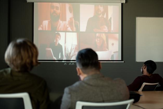 Diversi uomini d'affari sulla lavagna che fanno relazioni o rispondono alle domande del pubblico seduto nella sala conferenze o nell'auditorium