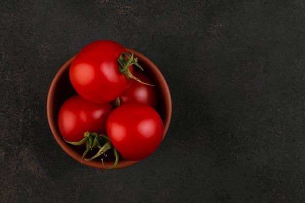 Parecchi pomodori ciliegia in una ciotola dell'argilla su oscurità