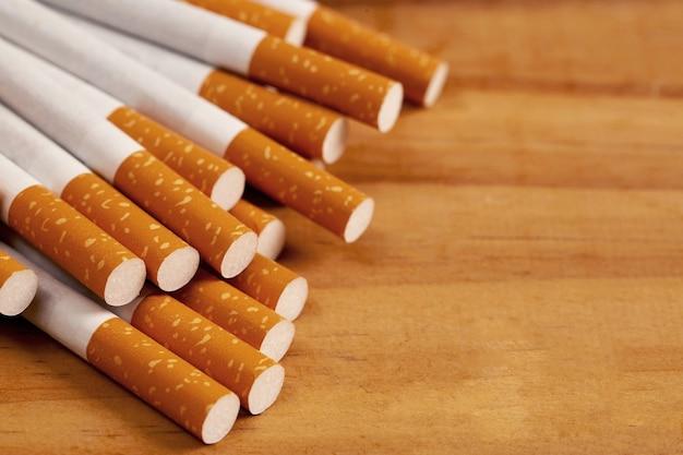 Diverse sigarette sono impilate su un pavimento di legno marrone e sono pericolose per i fumatori.