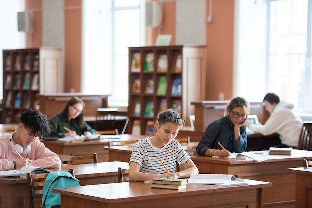 Diversi studenti universitari che prendono appunti seduti ai banchi e si preparano per un seminario o un compito a casa in biblioteca