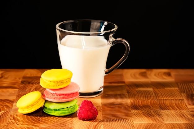 Diversi macarons colorati e una tazza trasparente con latte di mandorle su un tavolo di legno