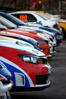 Diverse auto da rally colorate e allineate sull'asfalto.