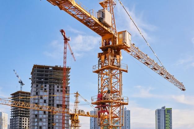 Diverse gru a torre da costruzione di diverse altezze in un cantiere durante la costruzione