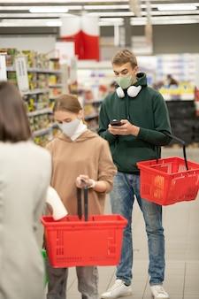 Diversi clienti con cestini della spesa in plastica in coda alla cassa del supermercato, uno di loro scorre nello smartphone