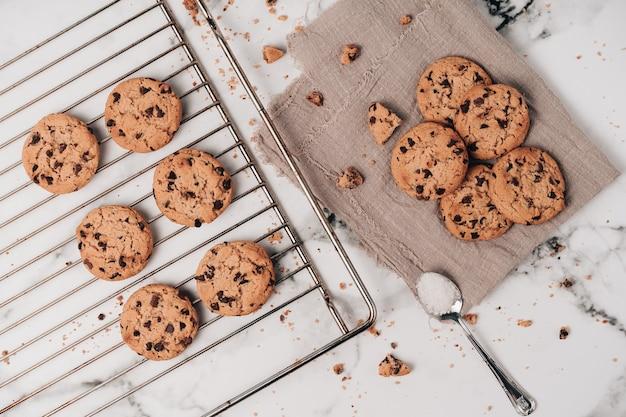 Diversi deliziosi biscotti con gocce di cioccolato appena sfornate sulla teglia e altri bocconcini, con pezzetti sparsi.