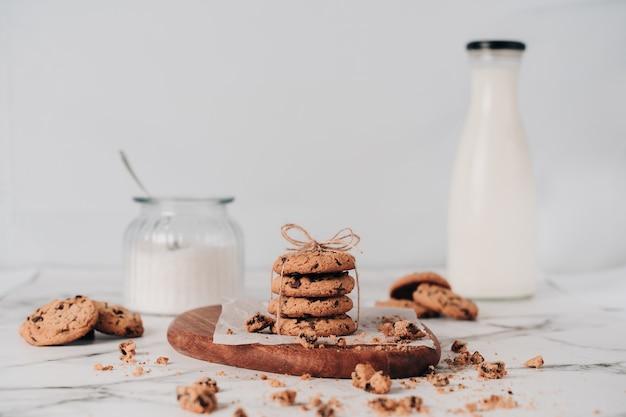 Diversi deliziosi biscotti con scaglie di cioccolato appena preparate su uno sfondo bianco con latte fresco e un barattolo con lo zucchero