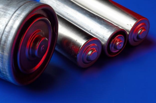 Diverse batterie su sfondo blu. avvicinamento.