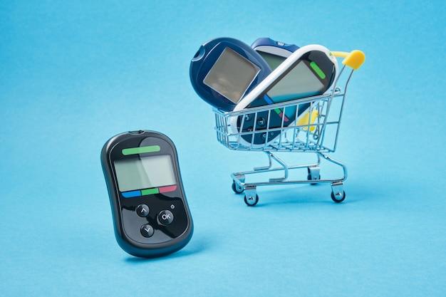 Diversi misuratori di glucosio in un carrello della spesa su uno sfondo blu, penne per siringhe da insulina per pazienti diabetici, luogo di copia, acquisto e vendita di dispositivi per il diabete