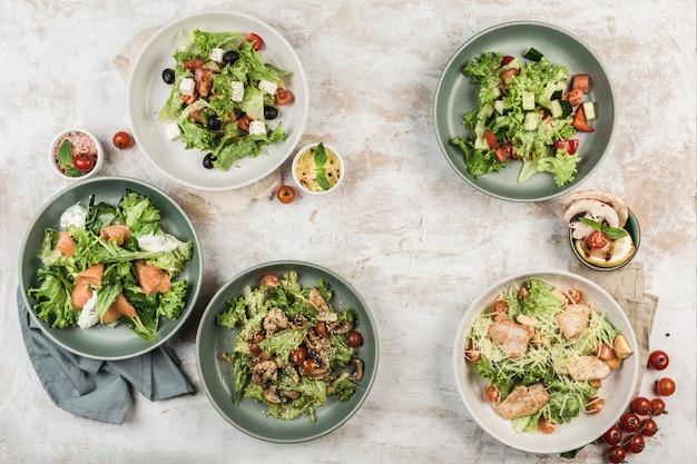Diversi piatti con insalate di verdure fresche con pesce e carne in diverse ciotole con il flusso dello chef su sfondo chiaro, vista dall'alto con copyspace. laici piatta. cibo del ristorante.